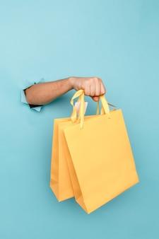 Mężczyzna trzyma w dłoni papierową torbę na zakupy przez otwór w niebieskim papierze