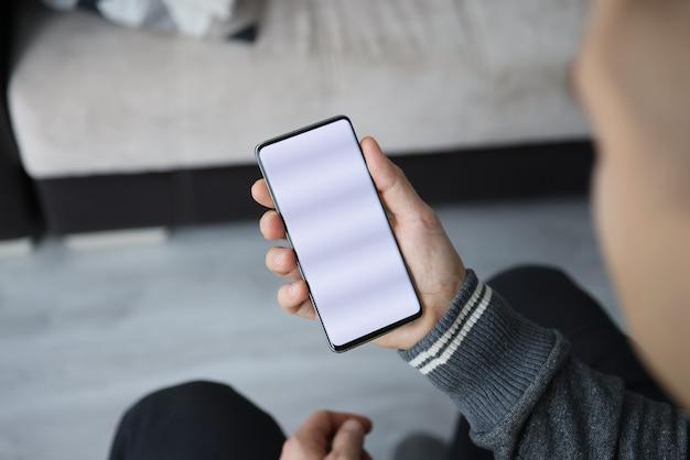 Mężczyzna trzyma w dłoni smartfon z białym ekranem