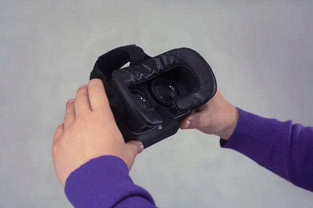 Mężczyzna trzyma w dłoniach okulary do wirtualnej rzeczywistości i wideo 360 stopni. kask vr na smartfona na jasnym tle.