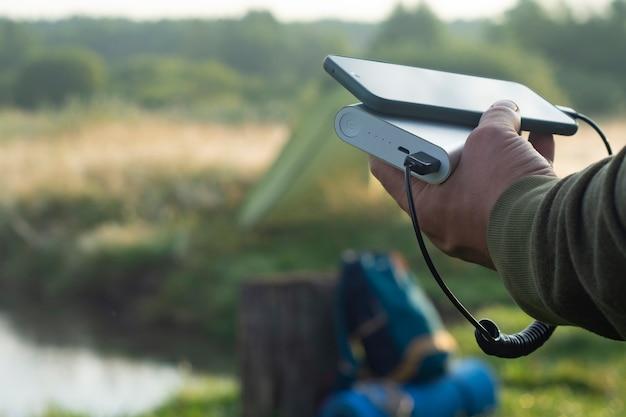 Mężczyzna trzyma w dłoniach smartfon i ładuje go powerbankiem na tle namiotu turystycznego w naturze. przenośna ładowarka podróżna.