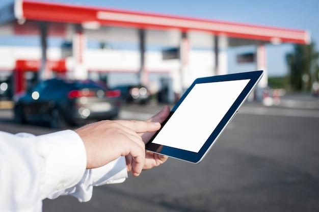 Mężczyzna trzyma w dłoniach tablet z białym ekranem na tle samochodu i stacji benzynowej. makieta technologii dla aplikacji i stron internetowych.