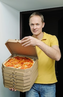 Mężczyzna trzyma w drzwiach pudełka z pizzą