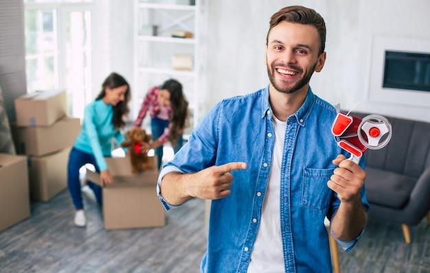 Mężczyzna trzyma w lewej ręce taśmę klejącą i wskazuje ją prawą ręką, podczas gdy jego żona i córka pakują swoje rzeczy na tle