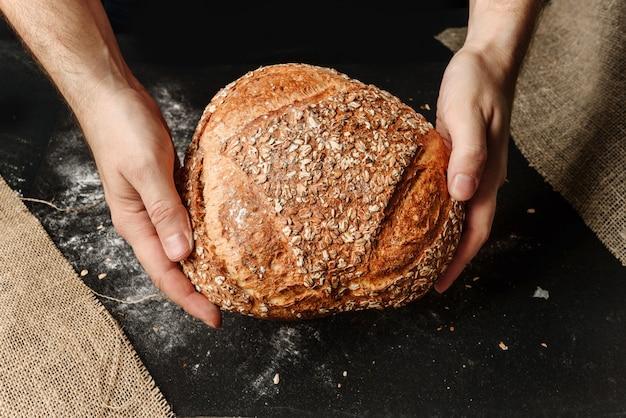 Mężczyzna trzyma w rękach bochenek rustykalnego chleba organicznego.
