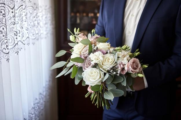 Mężczyzna trzyma w rękach bukiet ślubny