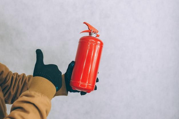 Mężczyzna trzyma w rękach czerwoną gaśnicę na białym.