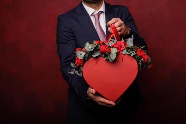 Mężczyzna trzyma w rękach czerwone pudełko róż
