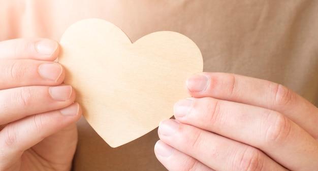 Mężczyzna trzyma w rękach drewniane ręcznie robione serce. walentynki, koncepcja 14 lutego