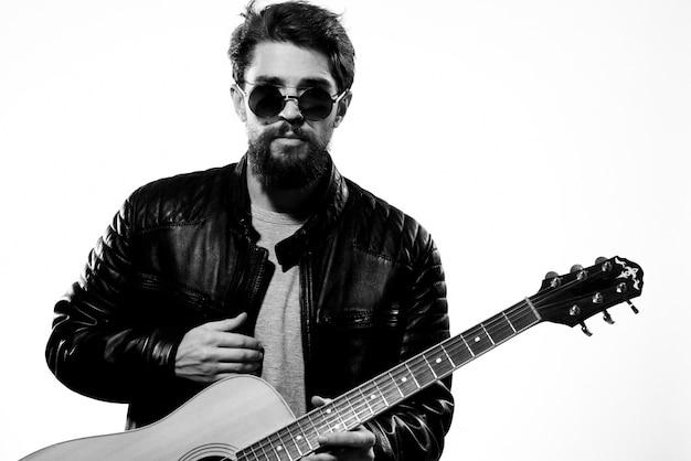 Mężczyzna trzyma w rękach gitarę czarna skórzana kurtka ciemne okulary występ muzyczny jasna ściana.