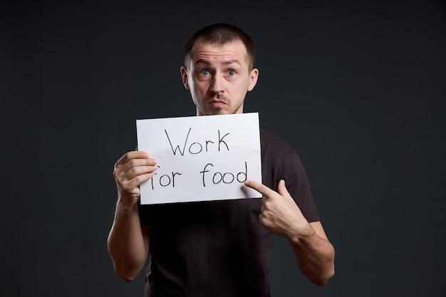 Mężczyzna trzyma w rękach kartkę papieru z plakatem z napisem pracuję dla żywności. uśmiech i radość, miejsce na tekst, miejsce na kopię