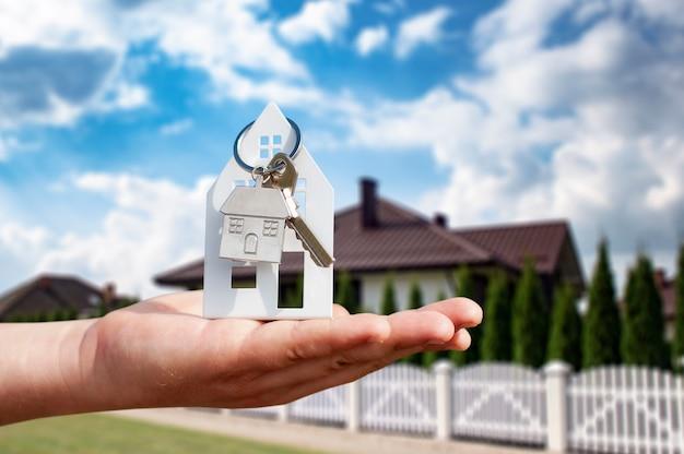 Mężczyzna trzyma w rękach klucze do domu na tle budynków mieszkalnych. koncepcja kupna i wynajmu mieszkań.