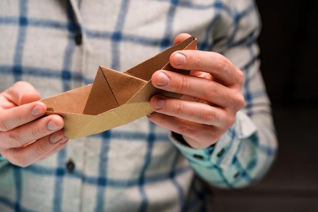 Mężczyzna trzyma w rękach łódź z papieru rzemieślniczego