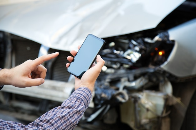 Mężczyzna trzyma w rękach makieta ekranu telefonu komórkowego po wypadku samochodowym. wywołanie usługi ubezpieczeniowej w aplikacji internetowej na miejsce wypadku samochodowego. smartfon przed rozbitym samochodem.