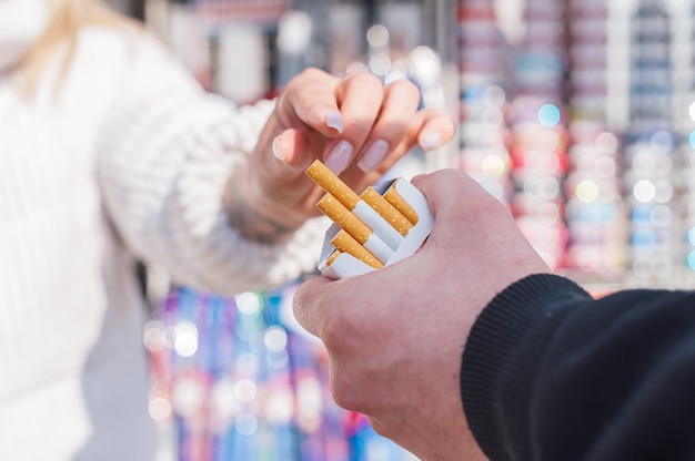 Mężczyzna trzyma w rękach paczkę papierosów i podaje dziewczynie papierosa.