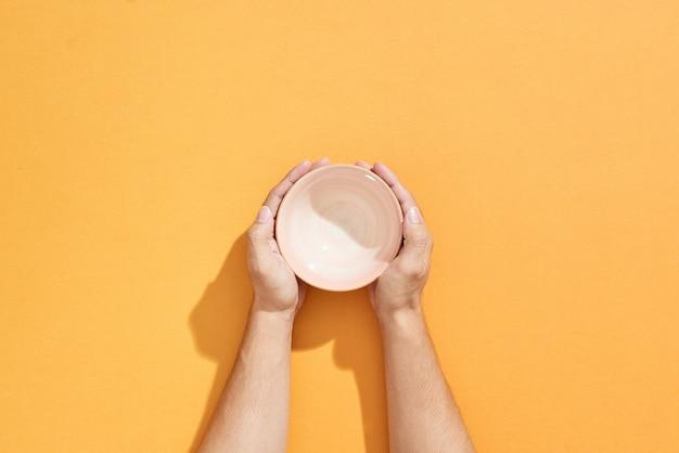 Mężczyzna trzyma w rękach pustą miskę na pomarańczowo