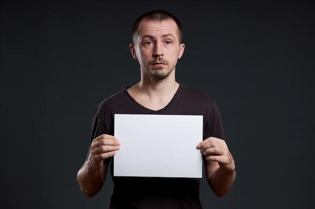 Mężczyzna trzyma w rękach pusty arkusz papieru plakatowego. uśmiech i radość, miejsce na tekst, miejsce na kopię