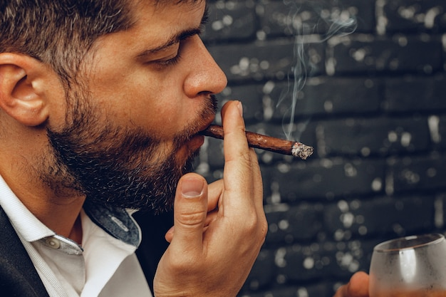 Mężczyzna trzyma w rękach szklankę whisky i zapalił papierosa z bliska