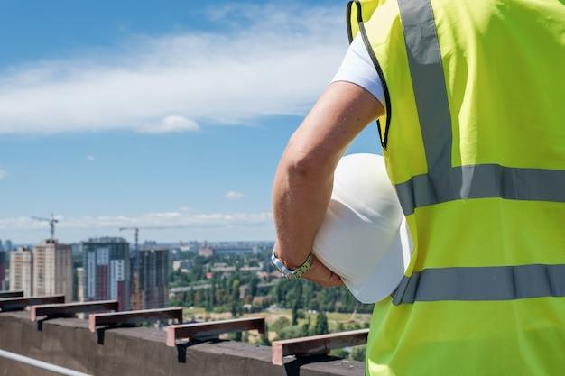 Mężczyzna trzyma w ręku biały kask na dachu budynku w budowie