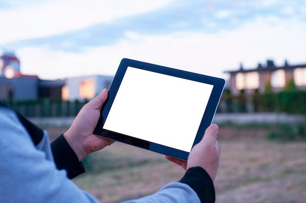 Mężczyzna trzyma w ręku czarny tablet z pustym białym ekranem w sąsiedztwie