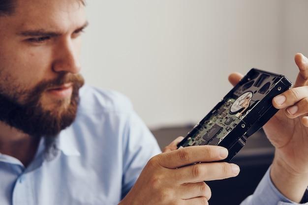 Mężczyzna trzyma w ręku dysk twardy. sprzęt komputerowy jest składnikiem komputera. wysokiej jakości zdjęcie