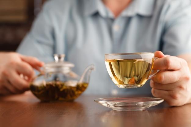 Mężczyzna trzyma w ręku filiżankę i oferuje herbatę