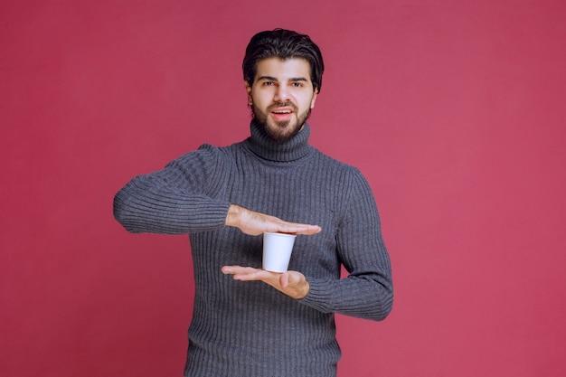 Mężczyzna trzyma w ręku jednorazową filiżankę kawy i czuje się pozytywnie.