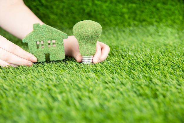 Mężczyzna trzyma w ręku mały eko dom i lampę na tle trawy.