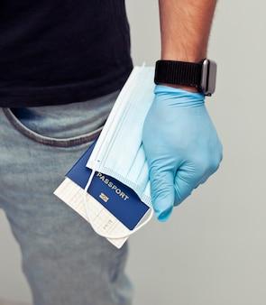 Mężczyzna trzyma w ręku paszport z biletem kolejowym i maskę medyczną w lateksowych rękawiczkach jako niezbędna rzecz w podróży w czasie post-19