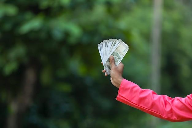 Mężczyzna trzyma w ręku pieniądze indyjskie
