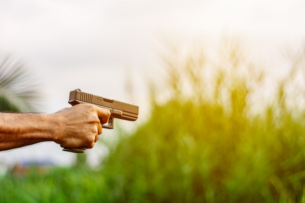 Mężczyzna trzyma w ręku pistolet. - pojęcie przemocy i przestępczości.
