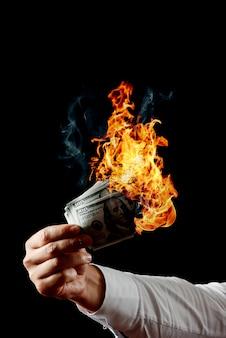 Mężczyzna trzyma w ręku płonące pieniądze