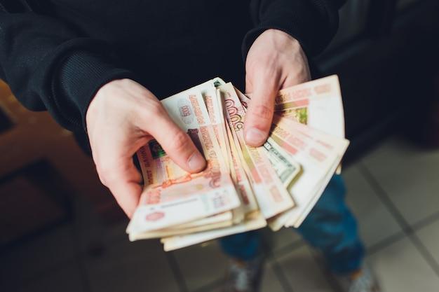 Mężczyzna trzyma w ręku ruble i dolary, biznesmen trzyma w ręku pieniądze.