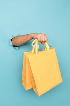 Mężczyzna trzyma w ręku żółtą papierową torbę na zakupy przez otwór w niebieskim papierze.