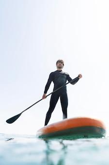 Mężczyzna trzyma wiosło z kostiumem surfingowym