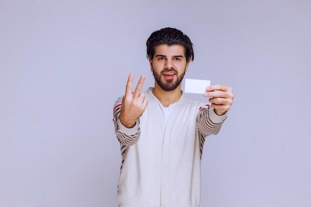 Mężczyzna trzyma wizytówkę i czyni znak przyjaźni.
