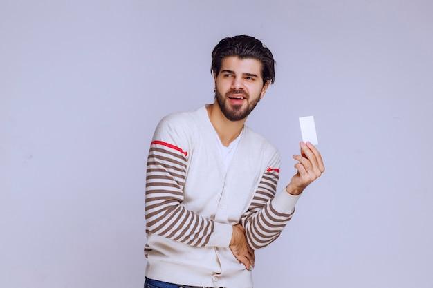 Mężczyzna trzyma wizytówkę i przedstawia ją lub odbiera.