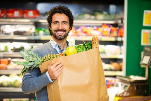 Mężczyzna trzyma worek zdrowej żywności w sklepie spożywczym