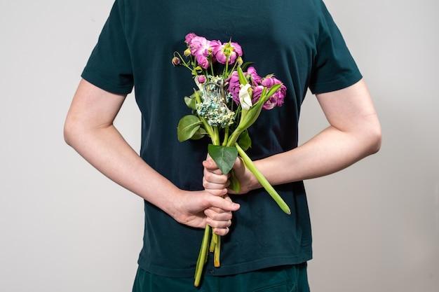 Mężczyzna trzyma za plecami bukiet zwiędłych kwiatów. pojęcie chciwości i skąpstwa