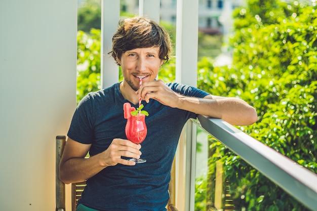 Mężczyzna trzyma zdrowego arbuza smoothie z mennicą i pasiastymi słoma na drewnianym tle