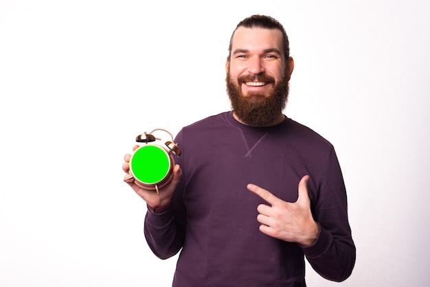 Mężczyzna trzyma zegar i wskazuje na niego uśmiechając się do kamery