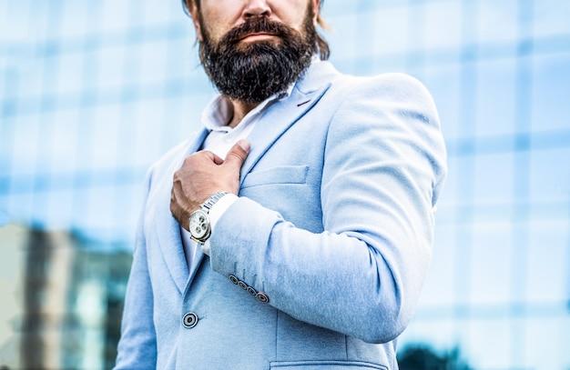 Mężczyzna trzyma zegarek. portret biznesmenem w garniturze, za pomocą zegarka na tle miasta. oglądaj w człowieku.