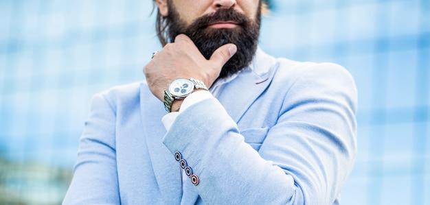 Mężczyzna trzyma zegarek. portret udanego biznesmena w garniturze