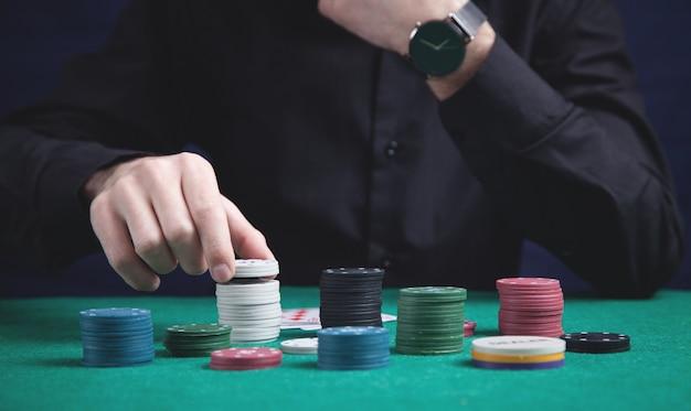 Mężczyzna trzyma żetony do pokera. kasyno