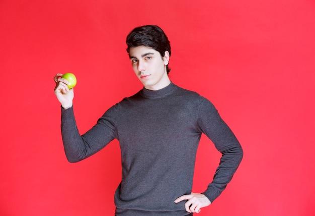 Mężczyzna trzyma zieloną mandarynkę i wskazuje na to