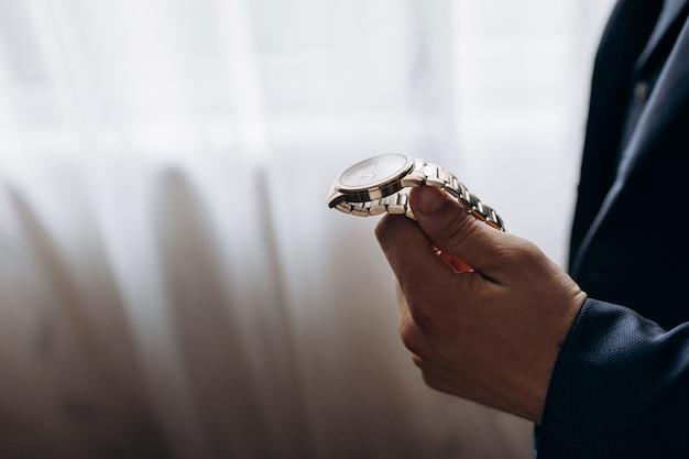Mężczyzna trzyma złoty zegarek