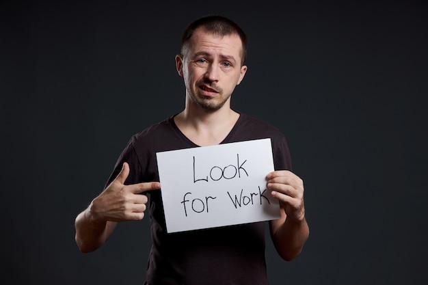 Mężczyzna trzyma znak z słowami szuka pracy