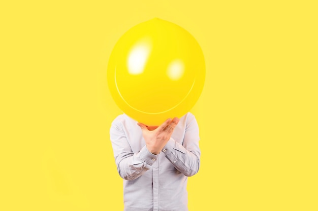 Mężczyzna trzyma żółty balon z emocją twarzy uśmiech zamiast głowy. koncepcje myślenia pozytywnego