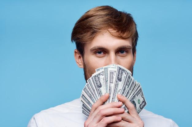 Mężczyzna trzyma zwitek pieniędzy w pobliżu zbliżenie bogactwa twarzy