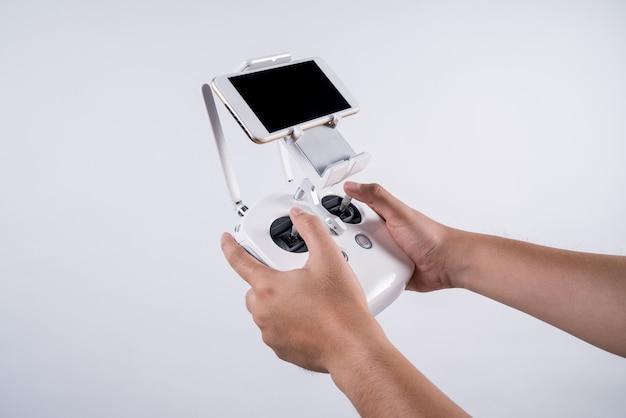 Mężczyzna trzymają drona pilot do tv z mądrze telefonem na białym tle, odizolowywającym.