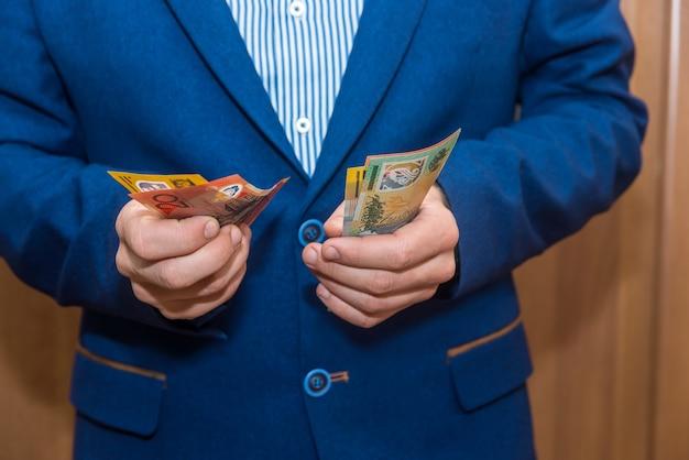 Mężczyzna trzymając się za ręce banknotów dolara australijskiego, zbliżenie